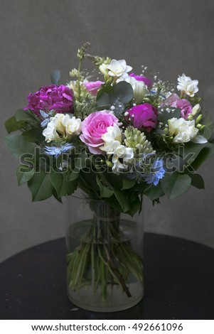 Flower arrangement for a girl. Is a gift with roses , orchids , freesia