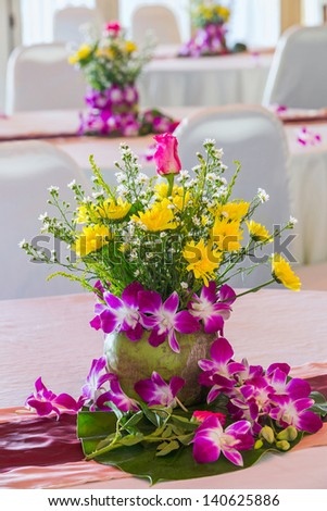 Flower arrangement in coconut vase on dining table in the party - stock photo
