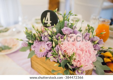 Flower arrangement of rose flowers and greenery is on the fest table, decorated with candles