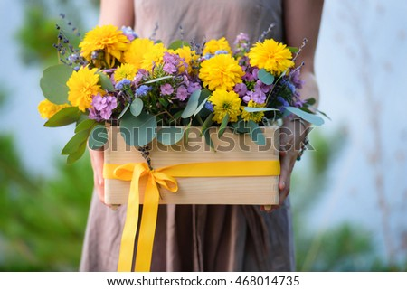Flower arrangement yellow purple flowers wooden stock photo edit flower arrangement with yellow and purple flowers in a wooden box in the hands of a mightylinksfo