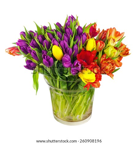 Flower bouquet from colorful tulips in glass vase isolated on white background. - stock photo