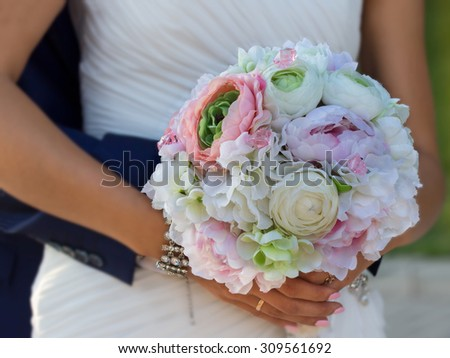flower bouquet in hands of bride which groom embracing  - stock photo