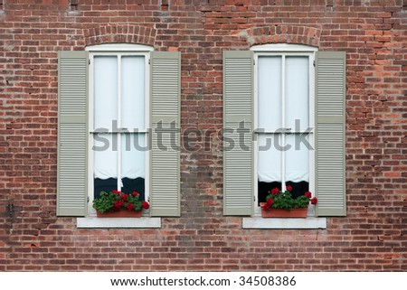 flower boxes in windows with shutters on old brick home - stock photo