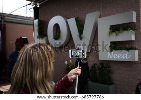 Flower festival in Keukenhof at spring in march 2017. Woman takes a picture of love inscription with her smartphone