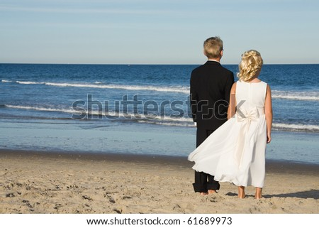Flower girl and ring bearer on the beach after a wedding.