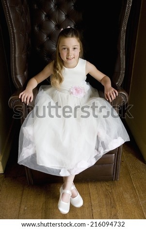 Flower girl (10-12) in armchair, smiling, portrait, elevated view