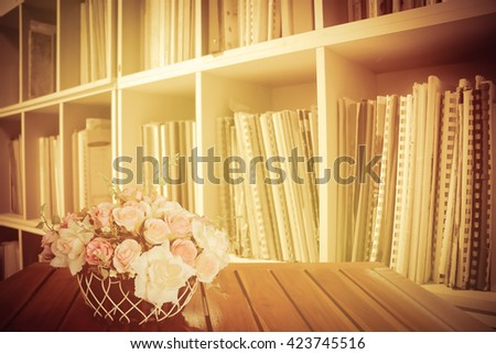flower in basket on the table with perspective bookshelf background - stock photo