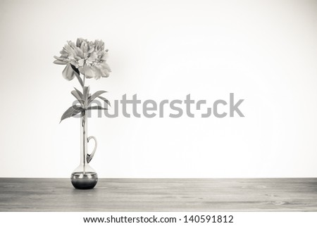Flower in vase on wooden table sepia photo for vintage background - stock photo