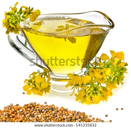 Flower Oil  in gravy boat and mustard flower isolated on white background - stock photo