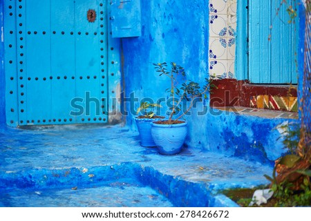 Flower pots on a street in Medina of Chefchaouen, Morocco, small town in northwest Morocco known for its blue buildings - stock photo