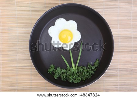 Flower shaped fried egg with parsley and spring onions - stock photo