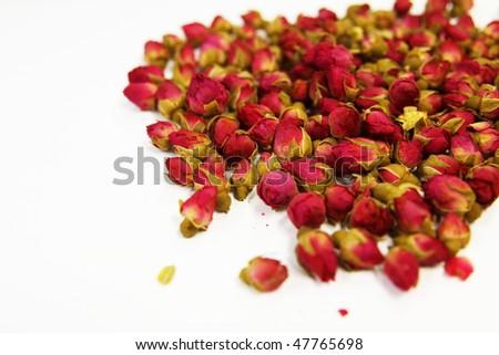 Flower tea of rose buds spilled on the desk. - stock photo