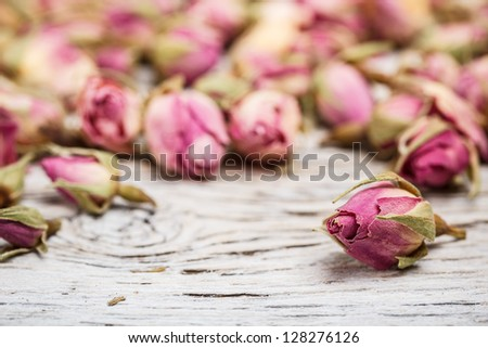 Flower tea rose buds on old wooden table - stock photo