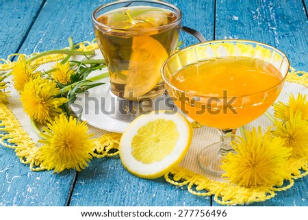 Flower tea with lemon, flowers and jam of dandelions on a blue wooden background - stock photo