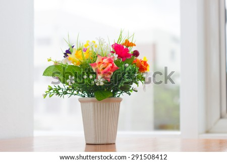 flower vase near the glass window - stock photo