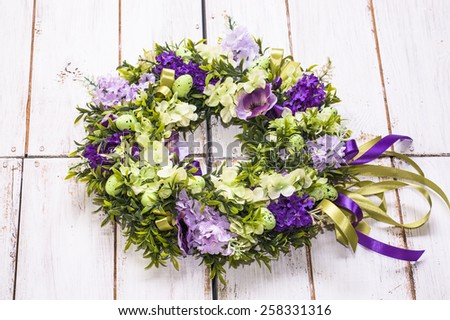 Flower wreath on white vintage wooden background - stock photo