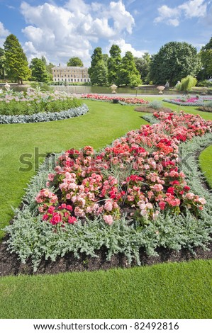 Flowerbed in the grounds of a large park with lake in the background - stock photo
