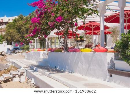 Flowering bougainvillea at restaurant on the beach of Mediterranean Sea - stock photo