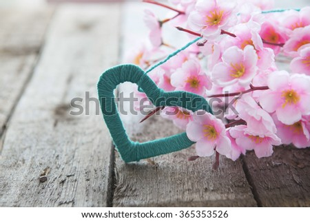 Flowering branch with pink delicate flowers on wooden surface. Declaration of love, spring. Wedding card, Valentine's Day greeting. Wedding bouquet, background. - stock photo