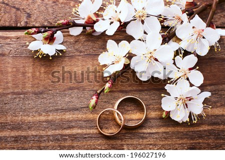 Flowering branch with white delicate flowers on wooden surface. Wedding rings. Wedding bouquet, background.  - stock photo