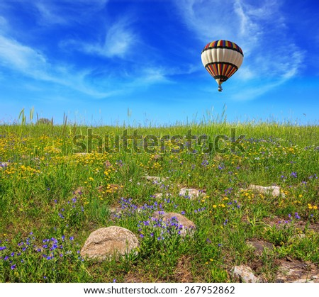 Flowering Golan Heights in a beautiful sunny day. In a clear sky flying big colorful balloon - stock photo