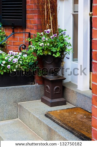 Flowering plants and ivy arranged in a planter urn by the front door. Seasonal display for spring and summer. - stock photo