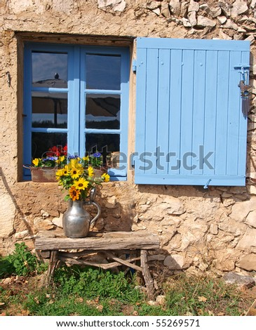 flowers and blue shutter on window of farmhouse in Provence - stock photo
