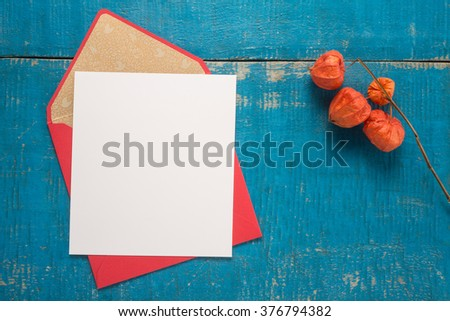Flowers and envelope on a wooden background  - stock photo