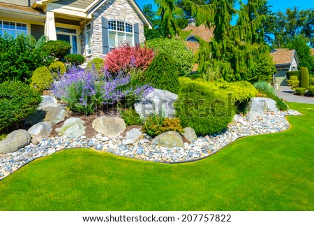 Flowers and stones in front of the house, front yard. Landscape design. - stock photo