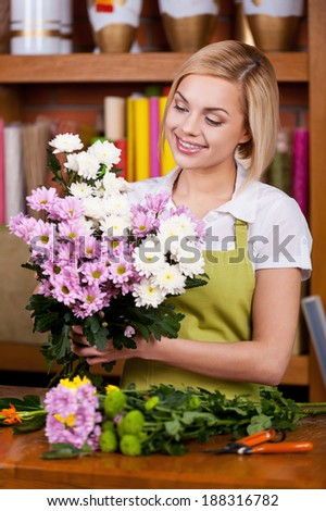 Flowers arrangement. Beautiful young blond hair woman in apron arranging flowers and smiling - stock photo