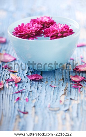 flowers floating in water in bowl sitting on weathered wood - stock photo