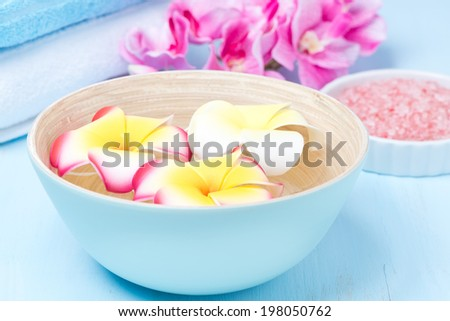 flowers in a blue bowl, towels and sea salt, close-up - stock photo