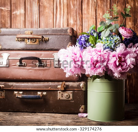 Flowers in a green vintage can and retro suitcases - stock photo