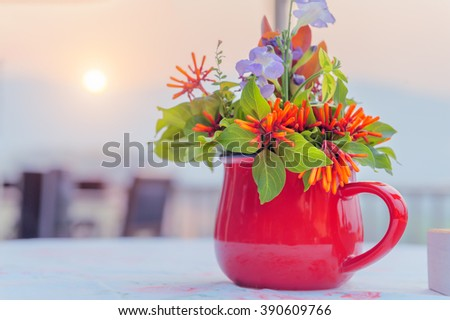 Flowers  in a red mug with sunset background