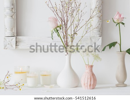 flowers in a vase and candles on white background