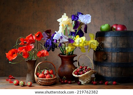 Flowers in a vase and fresh fruits on the wooden table - stock photo