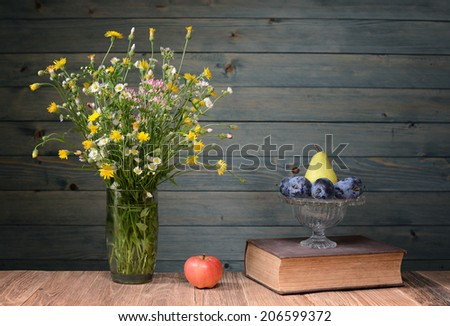 Flowers in a vase made ??of glass, books and fruit on the table - stock photo