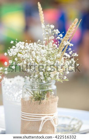 Flowers in mason jar with rope lace at an outdoors celebration - stock photo