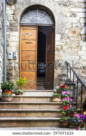 Flowers in pots on the stone steps medieval house in Assisi, Ita - stock photo