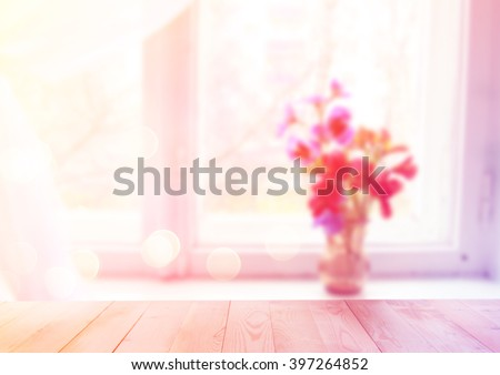 Flowers in vase on the window with wooden background - stock photo