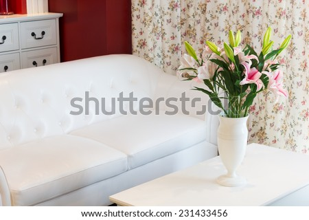 flowers in white vase on table,white leather sofa armchair & flowers pattern curtain, cozy living room - stock photo