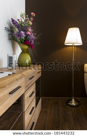 Flowers on the cupboard with lamp and brown wall - stock photo