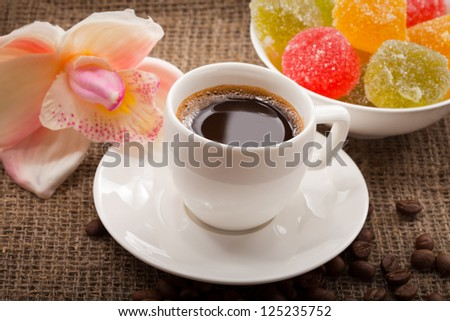 Flowers, orchid, cup of coffee and sweets. Close up on the fabric background. - stock photo