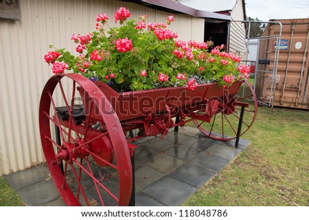 Flowers planted in Vintage farm equipment and utensils