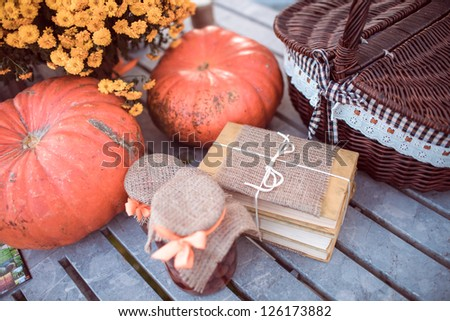 Flowers, pumpkins, jam, books and basket on garden table - stock photo