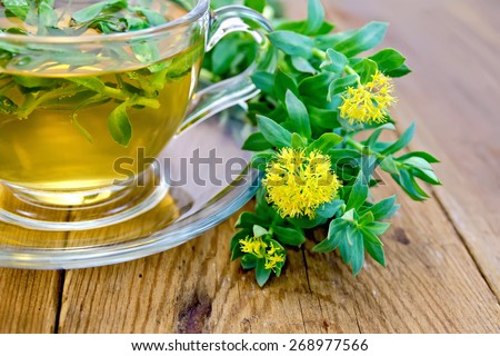 Flowers Rhodiola rosea, an herbal tea in a glass cup on a wooden boards background - stock photo