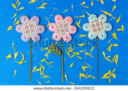 Flowers shaped cookie decorated with ornaments on blue background with yellow flower petals texture - stock photo