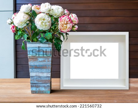 Flowers vase and blank white picture frame on wooden desktop - stock photo