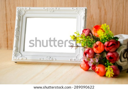 Flowers vase and vintage white picture frame on wooden desktop, clipping path - stock photo