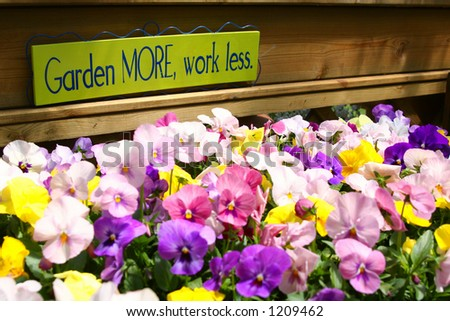 "Flowers with a ""Garden More, work less"" sign."